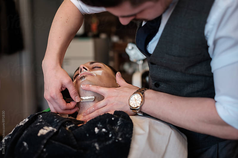 A gentleman barber shaves under a client's chin with a classic straight razor. by Riley J.B. for Stocksy United