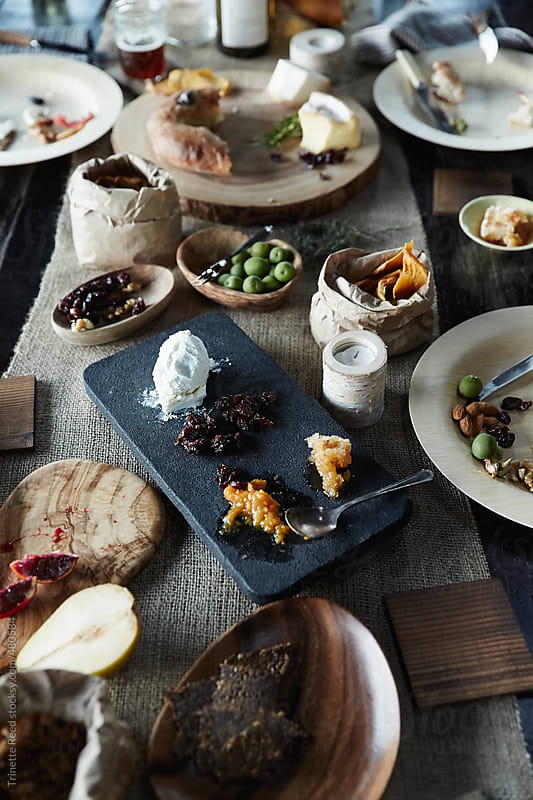 Messy food on wood table after dinner party by Trinette Reed for Stocksy United