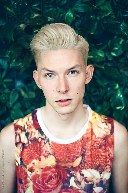 A portrait of a blonde man in a floral tank by Ania Boniecka for Stocksy United