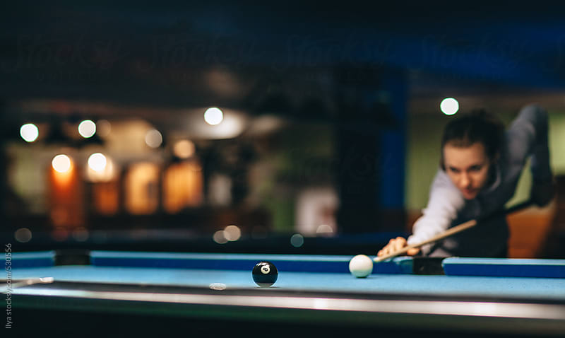 Young out of focus woman taking a shot in pool billiard game by Ilya for Stocksy United