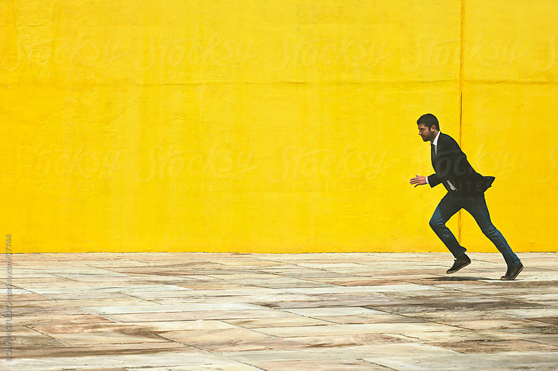 Businessman running on the street in front a yellow big wall. by BONNINSTUDIO for Stocksy United