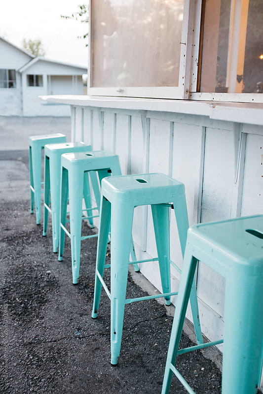 bright blue classically designed vintage colored stools outside old diner by Jesse Morrow for Stocksy United