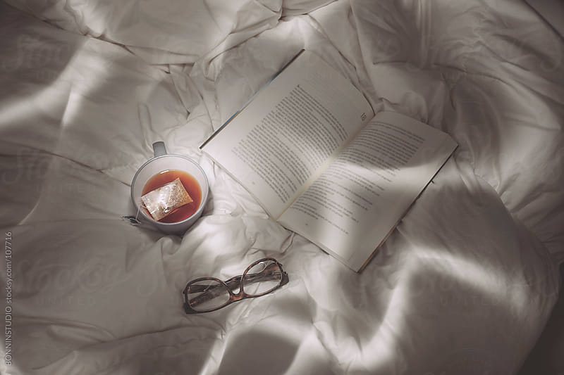 Closeup of a tea, book and glasses on the bed. Light painting. by BONNINSTUDIO for Stocksy United