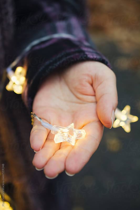 Hand holding Christmas lights by Pixel Stories for Stocksy United
