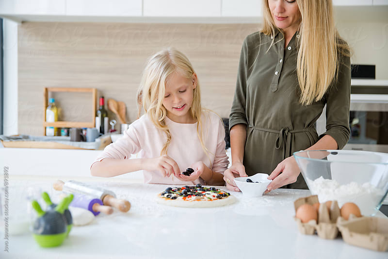 Mother and daughter making healthy pizza together by Jovo Jovanovic for Stocksy United