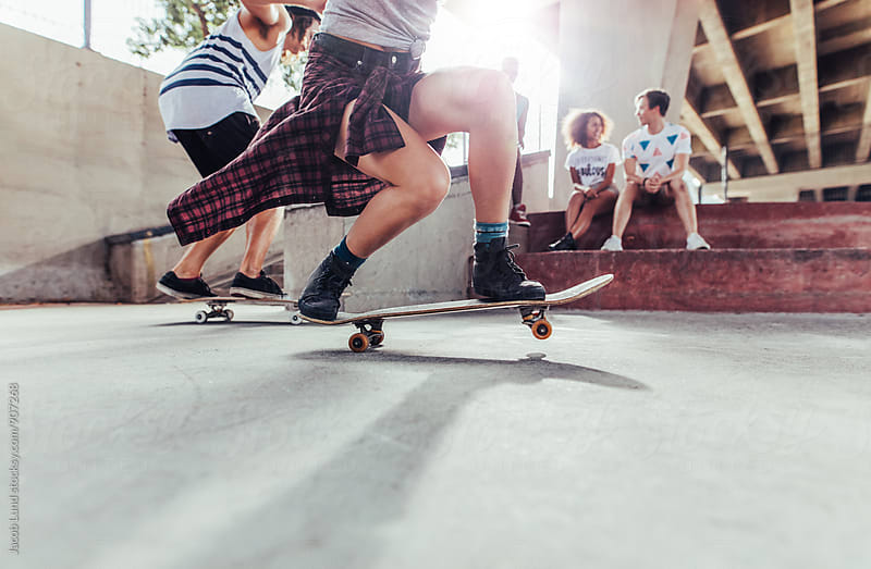 Young people practicing skateboard tricks at skate park by Jacob Ammentorp Lund for Stocksy United