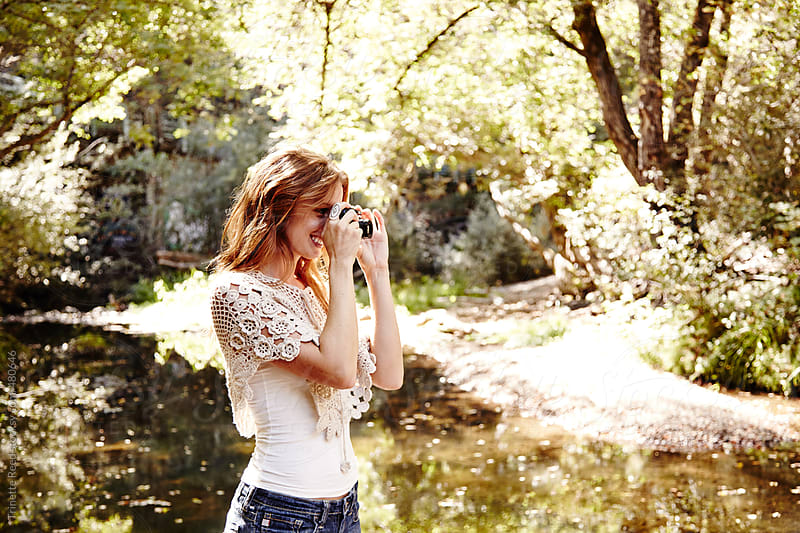 Beautiful redhead woman taking photos in nature in California  by Trinette Reed for Stocksy United