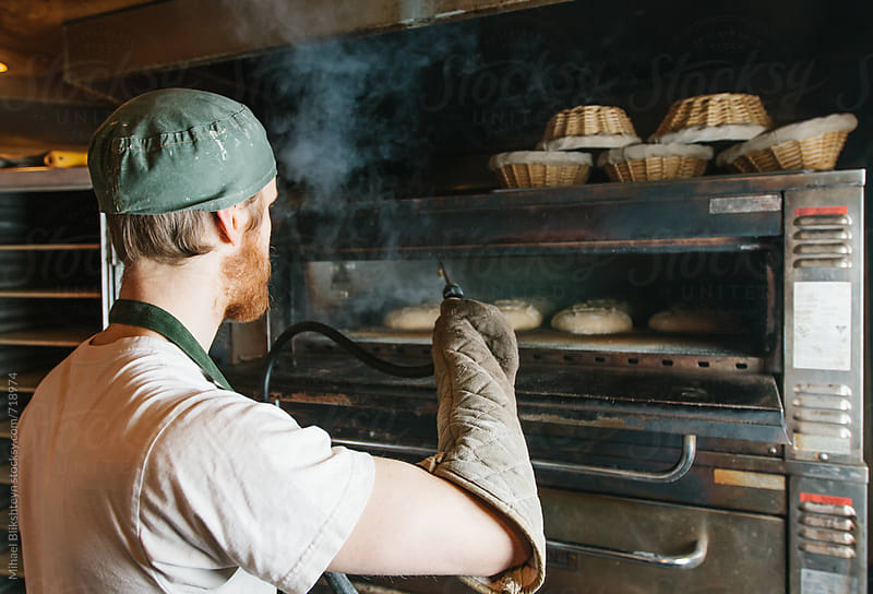Baker misting bread with water at a commercial artisinal bakery by Mihael Blikshteyn for Stocksy United
