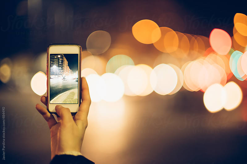 taking photo with a smartphone on street at night by Javier Pardina for Stocksy United