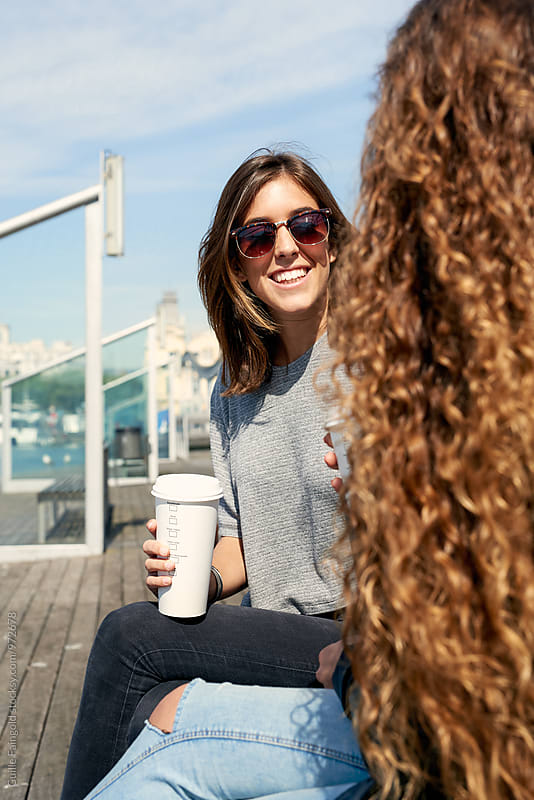 Two girlfriends with coffee to go at waterfront by Guille Faingold for Stocksy United