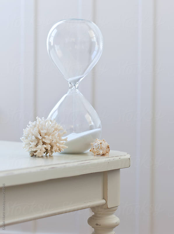 Hourglass, coral and shell on table by Daniel Hurst for Stocksy United