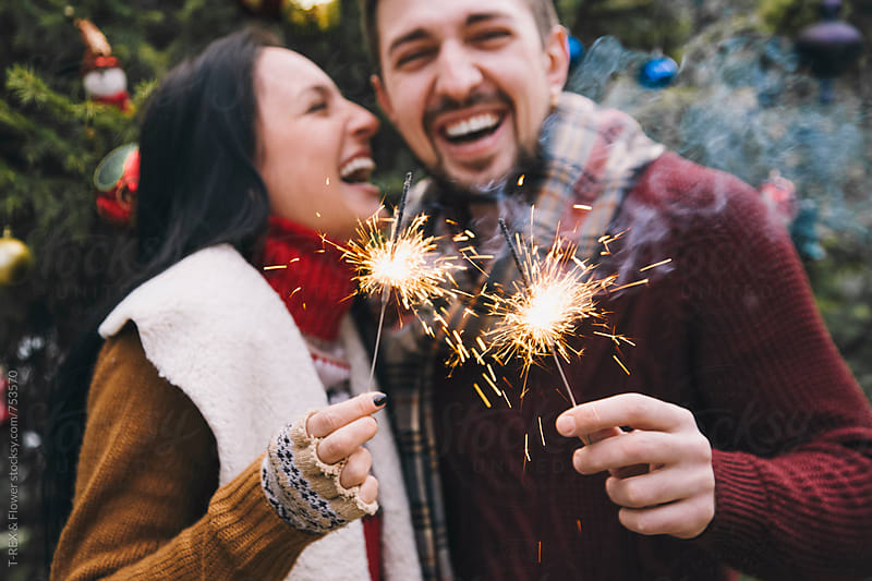 Couple laughing and holding Christmas sparklers. by T-REX & Flower for Stocksy United