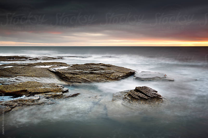 Blurred water on a rocky coastline by James Ross for Stocksy United