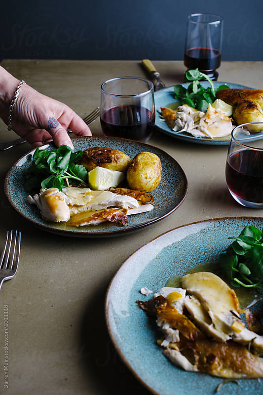 Roast chicken: With rosemary and lemon. Hand taking a plate of food. by Darren Muir for Stocksy United