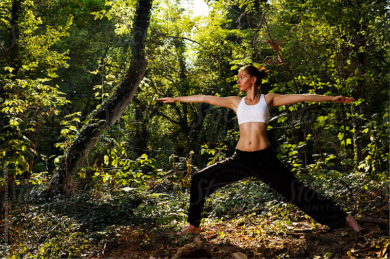 Woman doing yoga in nature. Warrior pose. by Aleksandra Kovac for Stocksy United