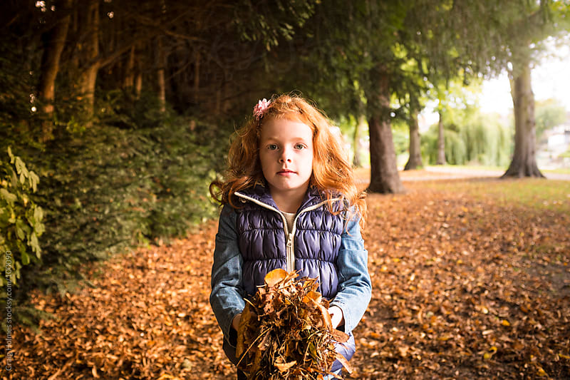 Seven year old girl holding fall leaves by Craig Holmes for Stocksy United