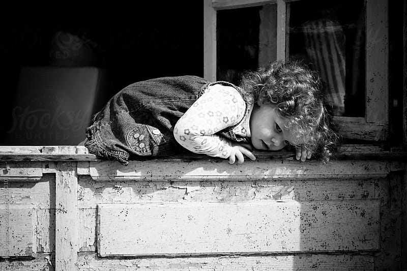 Girl climbing out of a window by Craig Holmes for Stocksy United