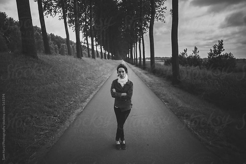 woman on a walking path under tall trees by Sam Hurd Photography for Stocksy United