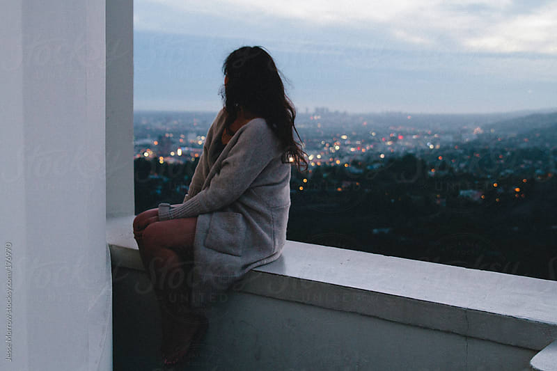 young woman sits on ledge looking out at city skyline by Jesse Morrow for Stocksy United