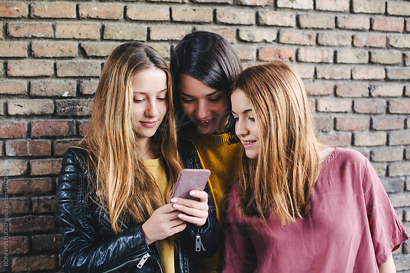 Teen friends looking their smartphone in front of a brick wall. by BONNINSTUDIO for Stocksy United