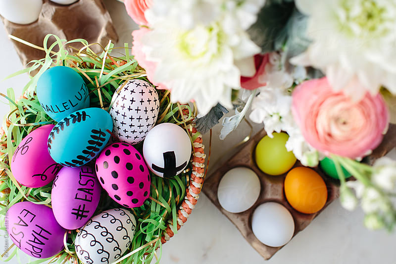 Basket of colorful easter eggs with fresh floral blooms by Kristen Curette Hines for Stocksy United