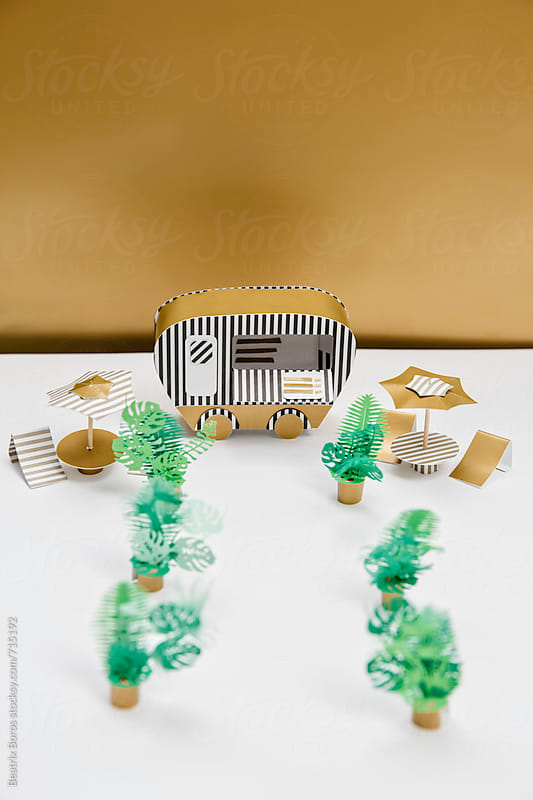 Paper plants showing the way to a food track  in front of a golden wall by Beatrix Boros for Stocksy United