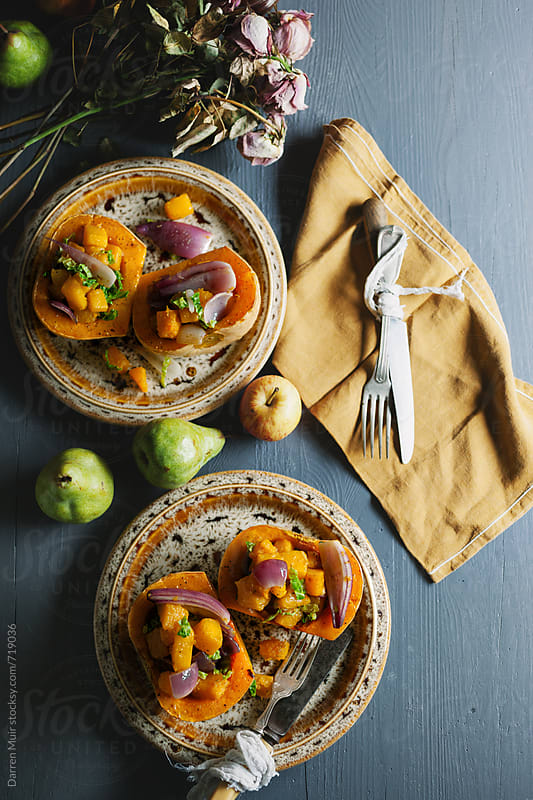 Roasted squash meal on two plates with autumnal fruits and dried summer flowers on a table. by Darren Muir for Stocksy United