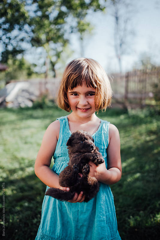 Young girl carrying a puppy  by Boris Jovanovic for Stocksy United