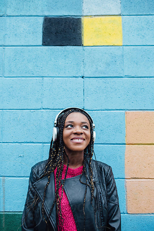 Happy girl listening to music with headphones by michela ravasio for Stocksy United