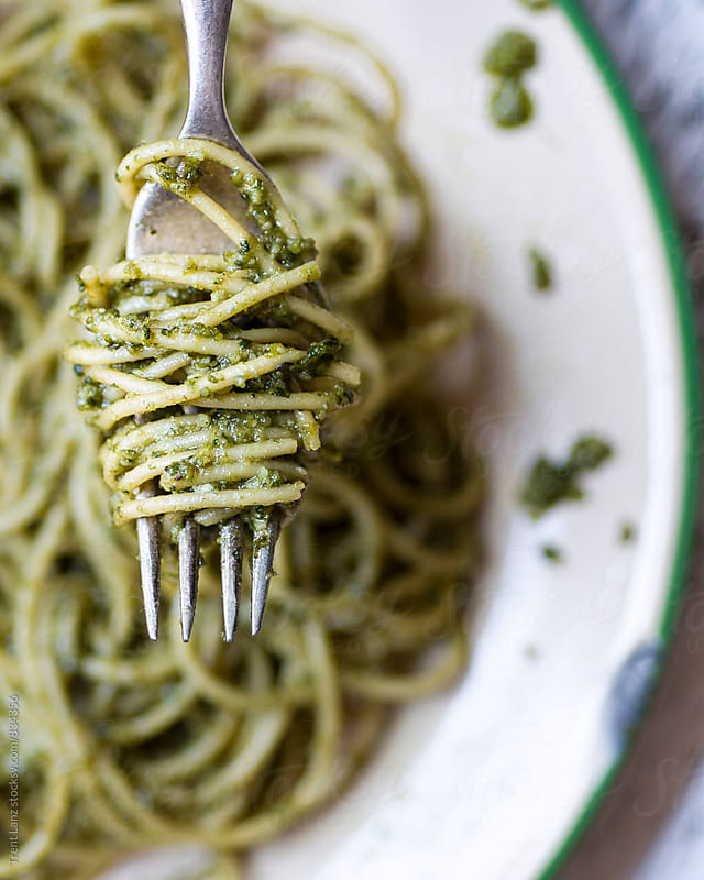 Close-up of Pesto Pasta rolled on a fork in a Bowl by Trent Lanz for Stocksy United
