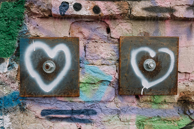 Two hearts painted on a brick wall by Alberto Bogo for Stocksy United