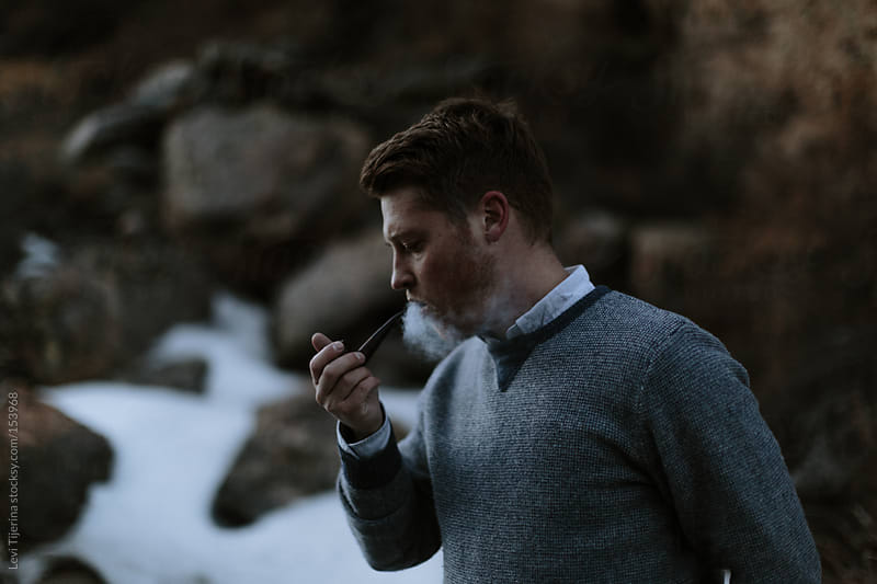 smoking a pipe in the mountains by Levi Tijerina for Stocksy United