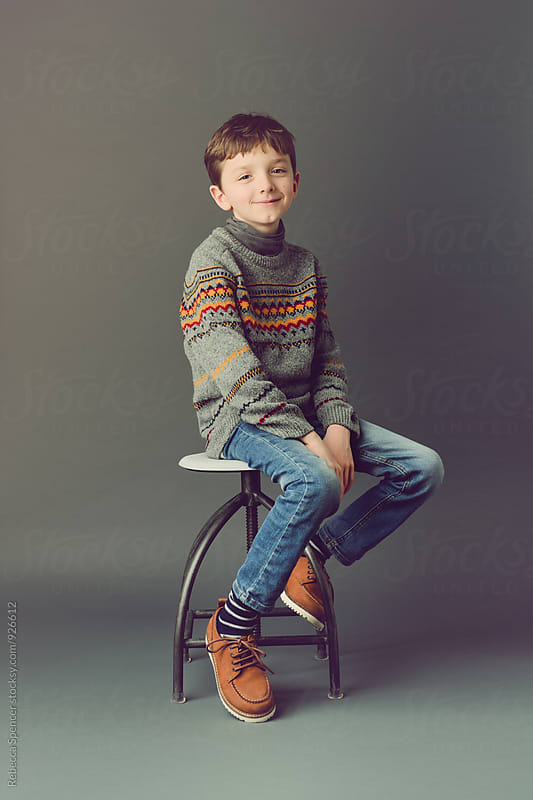 Happy portrait of young boy sitting on a stool with simple grey background by Rebecca Spencer for Stocksy United