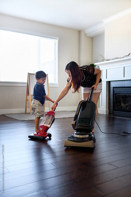 Asian boy helping his mother vacuuming the floor at home by Suprijono Suharjoto for Stocksy United