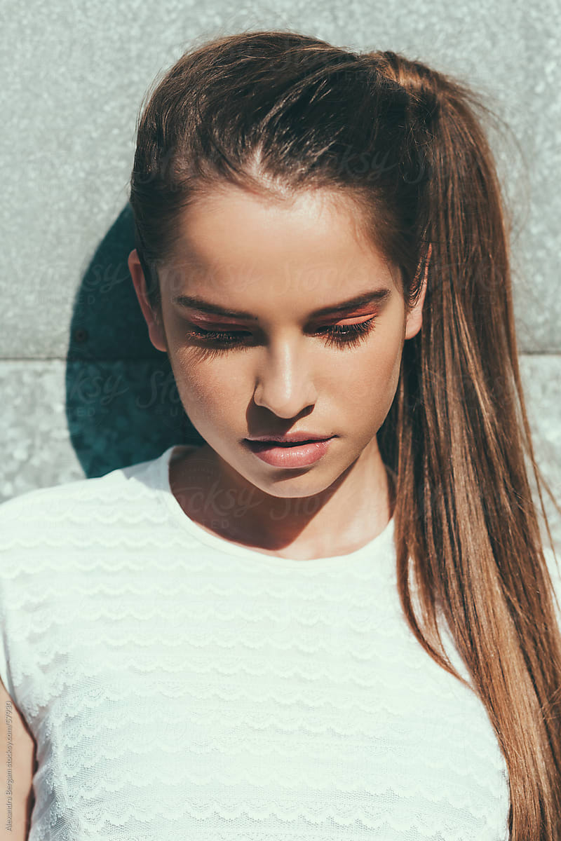 sunlit portrait of a young woman looking down stocksy united