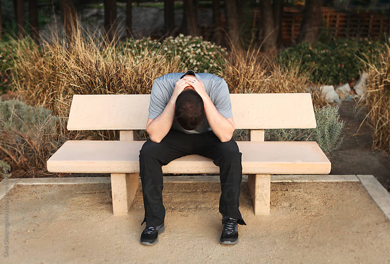 Man sitting on bench outdoors with head down and hands clasped behind neck by Dina Giangregorio for Stocksy United