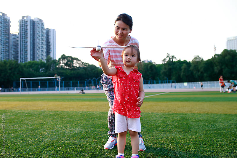 little asian girl playing with her plane toy in the football field by cuiyan Liu for Stocksy United