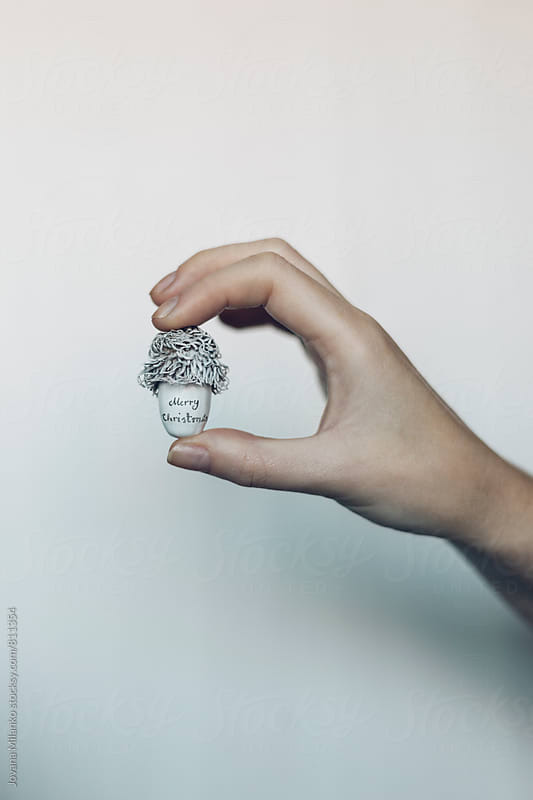 Woman's hand holding acorn painted in white with Merry Christmas handwritten on it  by Jovana Milanko for Stocksy United