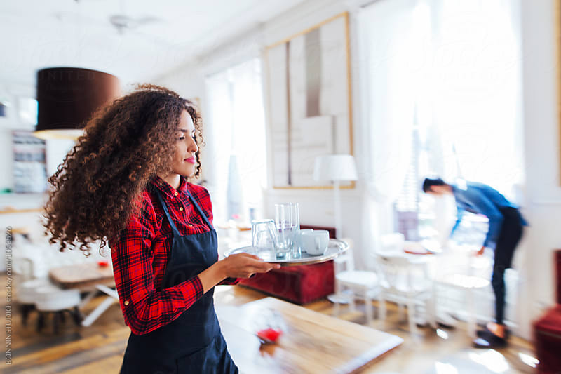 Movement image of young woman wearing an apron holding a tray  in a beautiful coffee shop. by BONNINSTUDIO for Stocksy United