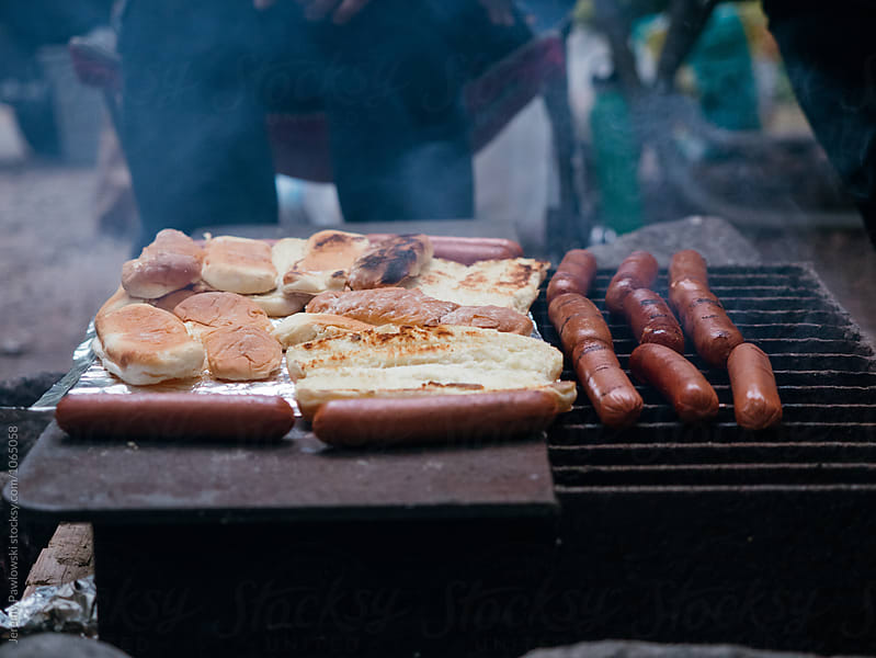 Hot dogs and buns cooking over campfire in National Park by Jeremy Pawlowski for Stocksy United