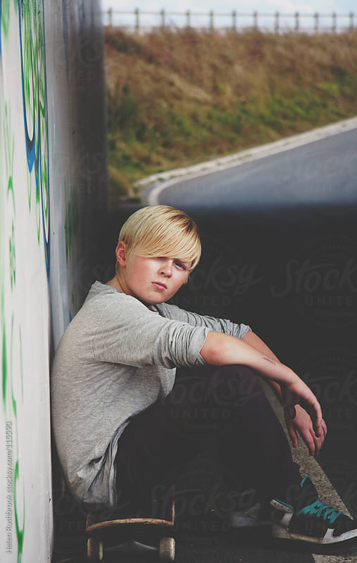 A teenage boy with his skateboard in  heavily graffitied location by Helen Rushbrook for Stocksy United