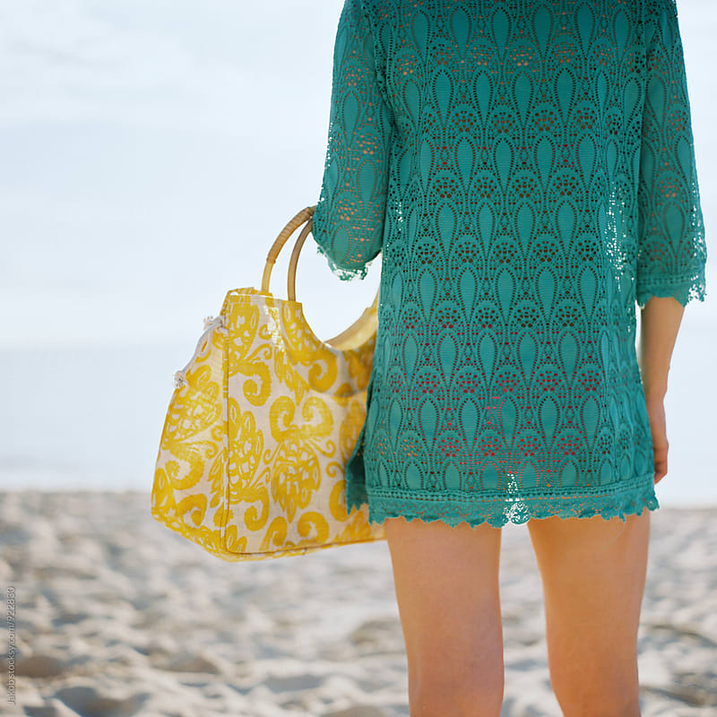 Woman with a bathing suit cover up and yellow purse standing on a beach by Jakob for Stocksy United