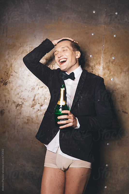 Half-dressed men in a suit holding bottle of champagne and laugh  by Andrey Pavlov for Stocksy United