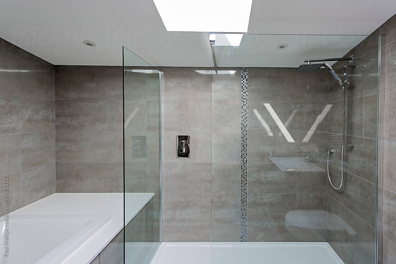 Contemporary bathroom with glass shower partition. by Paul Phillips for Stocksy United