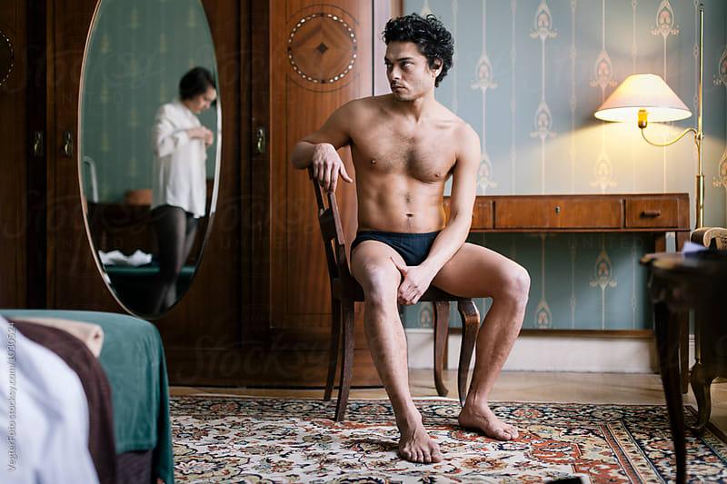 Man sitting in Hotel room in his underwear by VegterFoto for Stocksy United