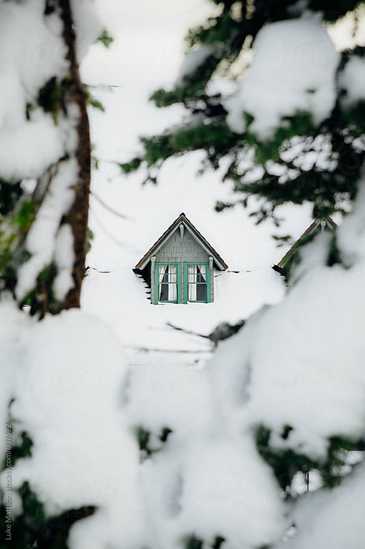 Dormer Window On Top Of Mountain Lodge Roof Covered In Snow Seen Through Pine Trees by Luke Mattson for Stocksy United