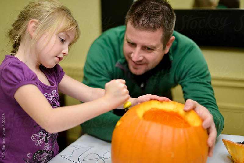 Father and Daughter Carving Orange Halloween Pumpkin by JP Danko for Stocksy United