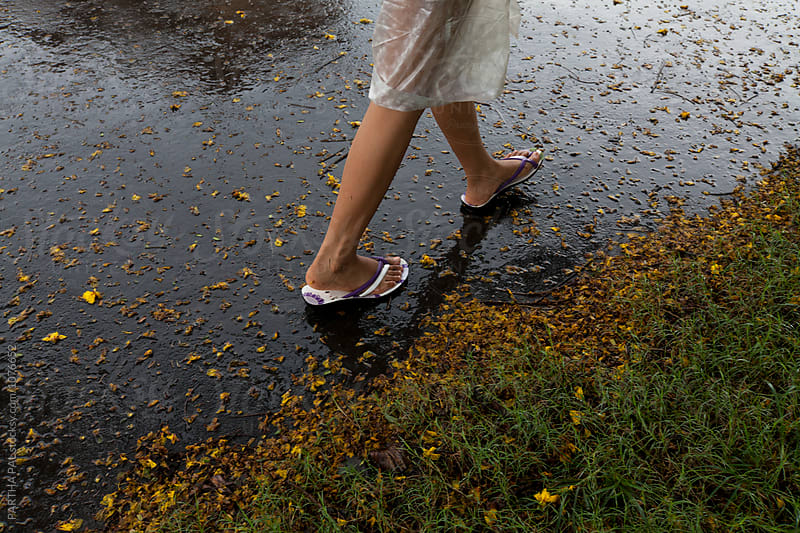 Teenage girl walking through rain wet path by PARTHA PAL for Stocksy United