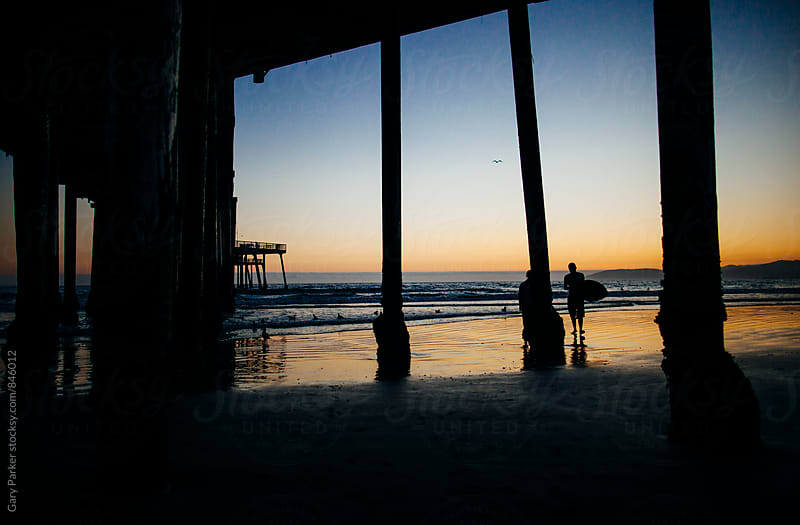 A silhouette of a surfer standing underneath a pier as the sunsets by Gary Parker for Stocksy United