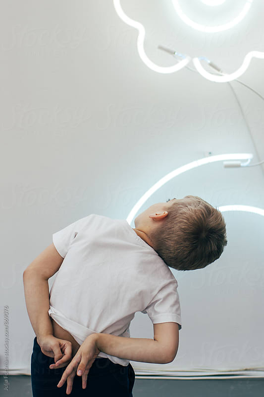 A boy twists his hands behind his back as he looks up at LED tubes on a wall. by Julia Forsman for Stocksy United